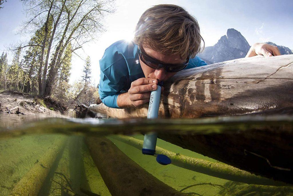 Persona beve dal lago con filtro lifestraw